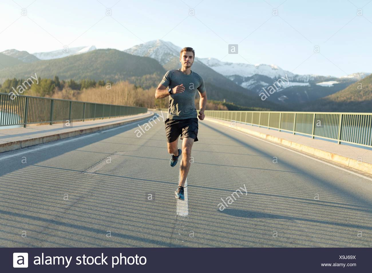 Young man, running on road, mountains behind him, front view - Stock Image