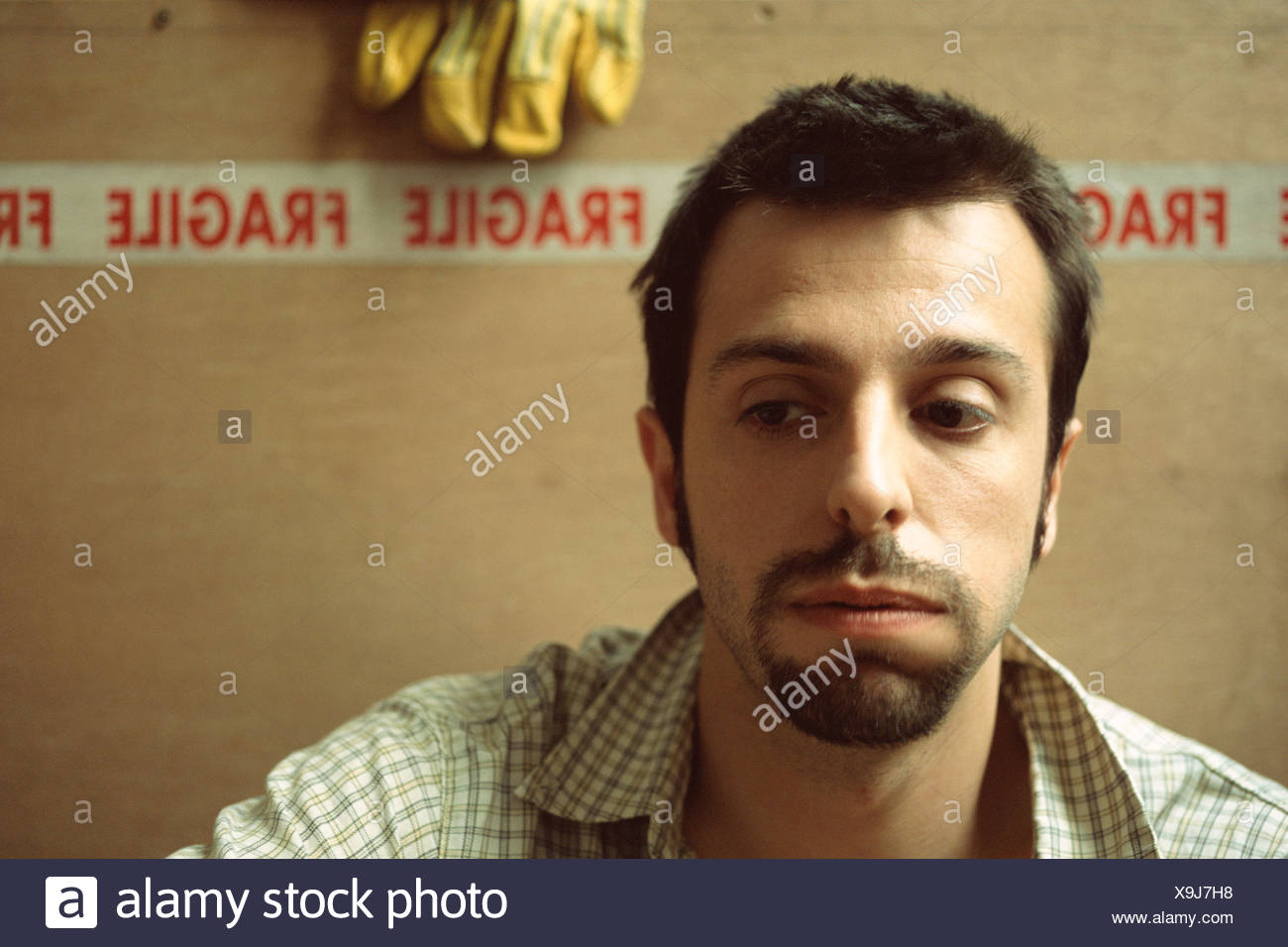 Man sitting in front of cardboard boxes - Stock Image