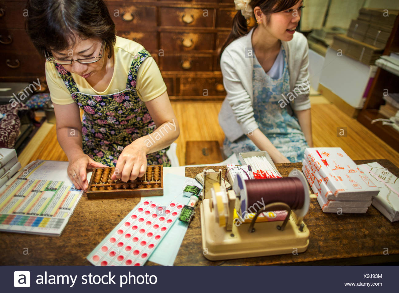 A small artisan producer of specialist treats, sweets called wagashi. Two women working packing sweet boxes for delivery. - Stock Image