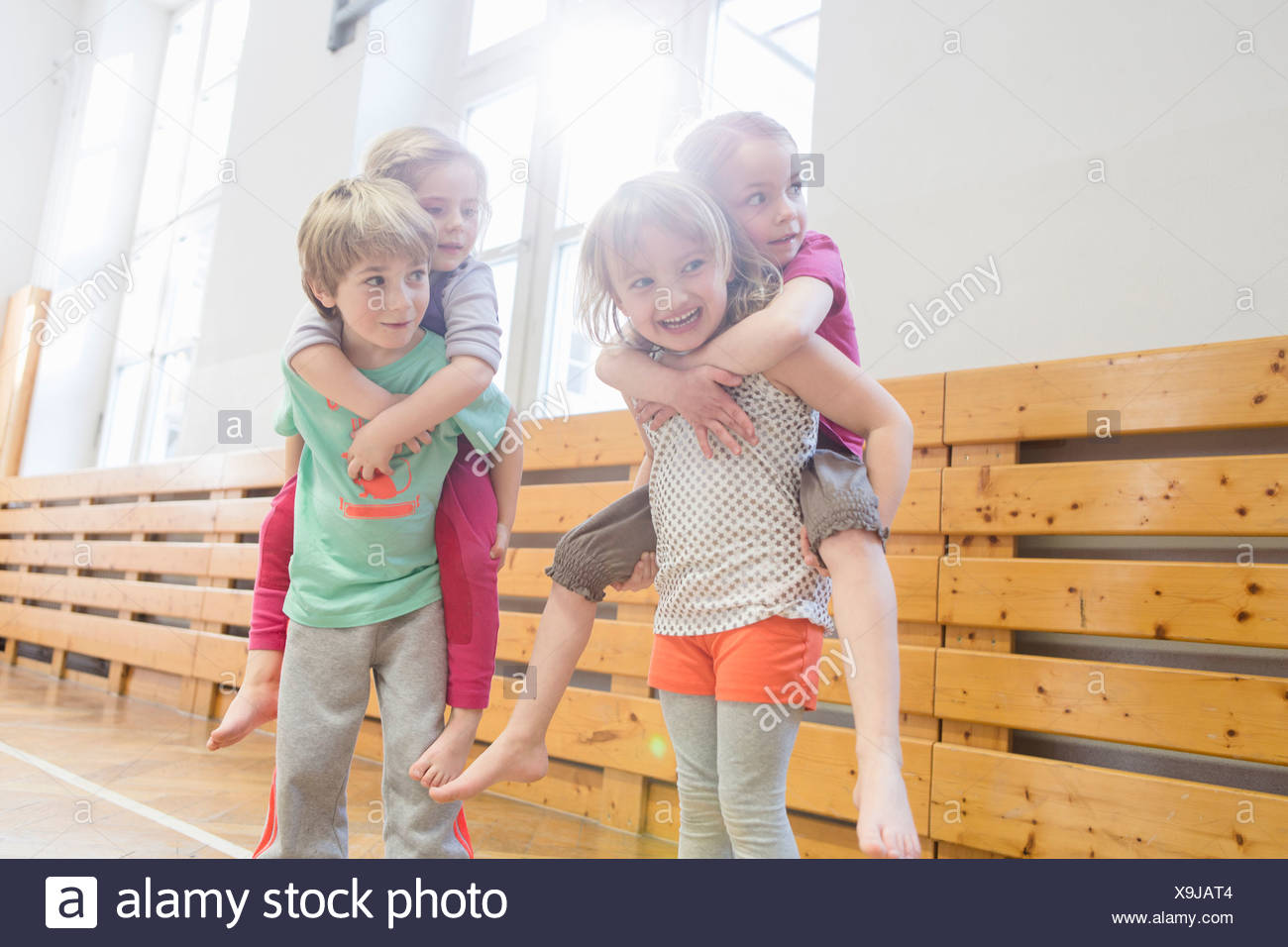Children giving friends a piggy back - Stock Image