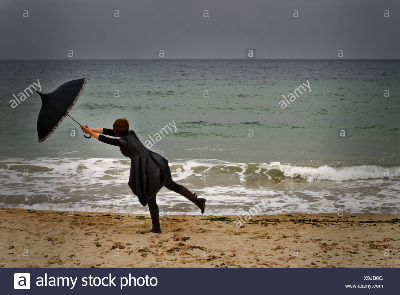 Woman with umbrella on beach on a Windy day - Stock Image