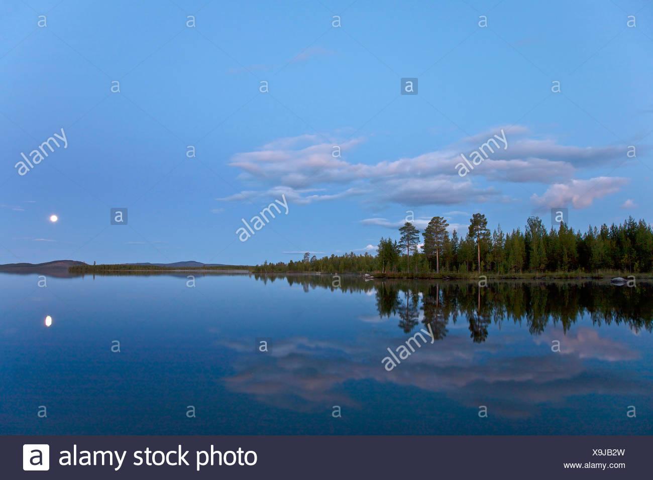 full moon mirroring in a lake in evening light, Sweden, Lapland, Norrbottens Laen, Kvikkjokk - Stock Image