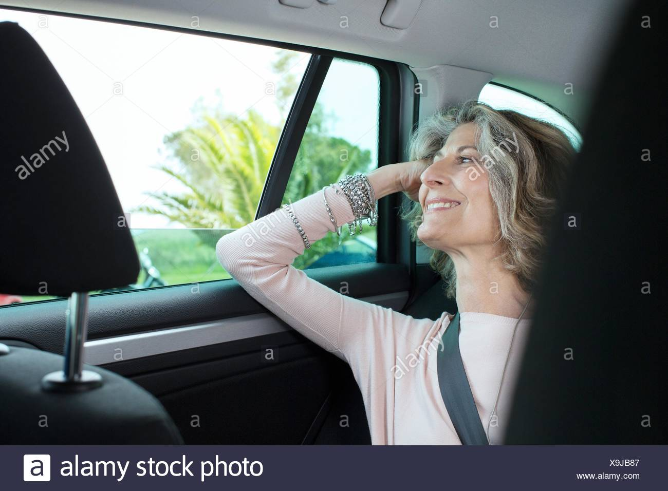 Senior businesswoman looking through car window - Stock Image