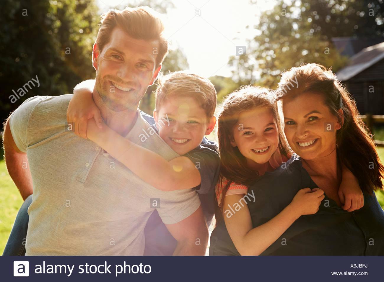 Portrait Of Parents Giving Children Piggyback In Garden - Stock Image