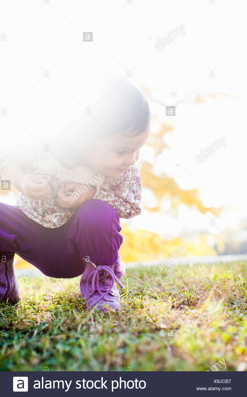 Child squatting looking down at grass - Stock Image