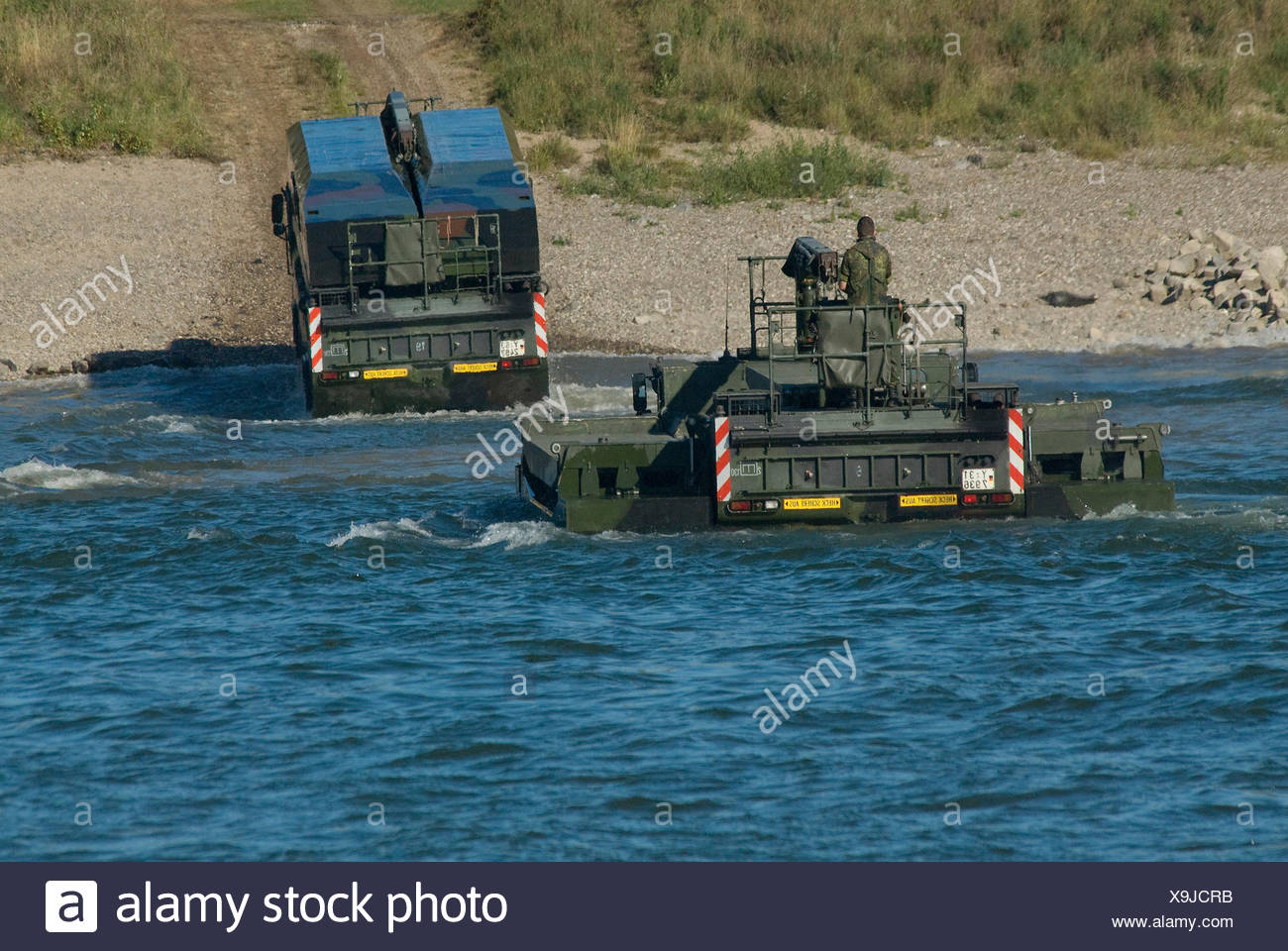 Two M3 amphibious vehicles of the Bundeswehr, federal army, emerging from the Rhine, one with folded wings - Stock Image