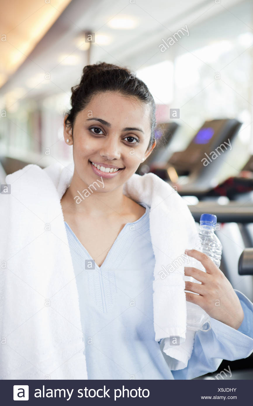 Woman with towel and water bottle in gym - Stock Image
