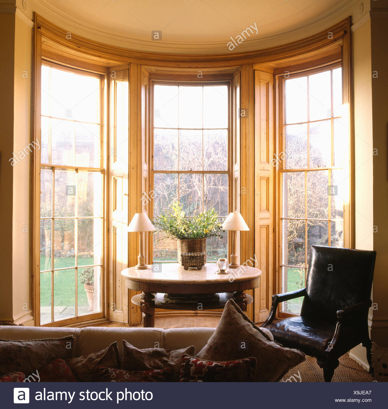 Leather Chair And Small Antique Table In Bay Window In Eighties Living Room Stock Photo Alamy