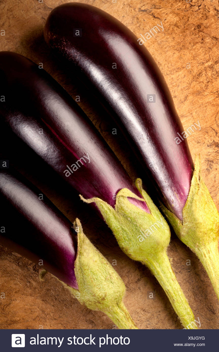Three Aubergine on textured background - Stock Image