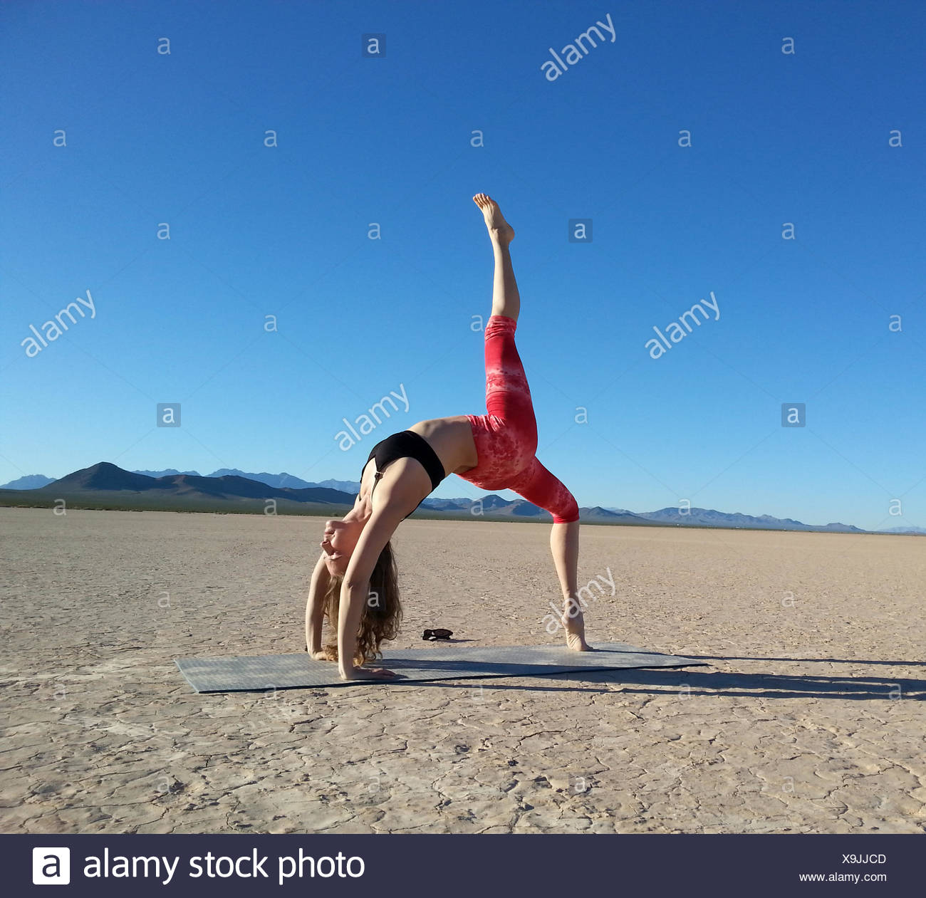 Woman doing a one legged wheel pose in a dry lake, Nevada, America, USA Stock Photo