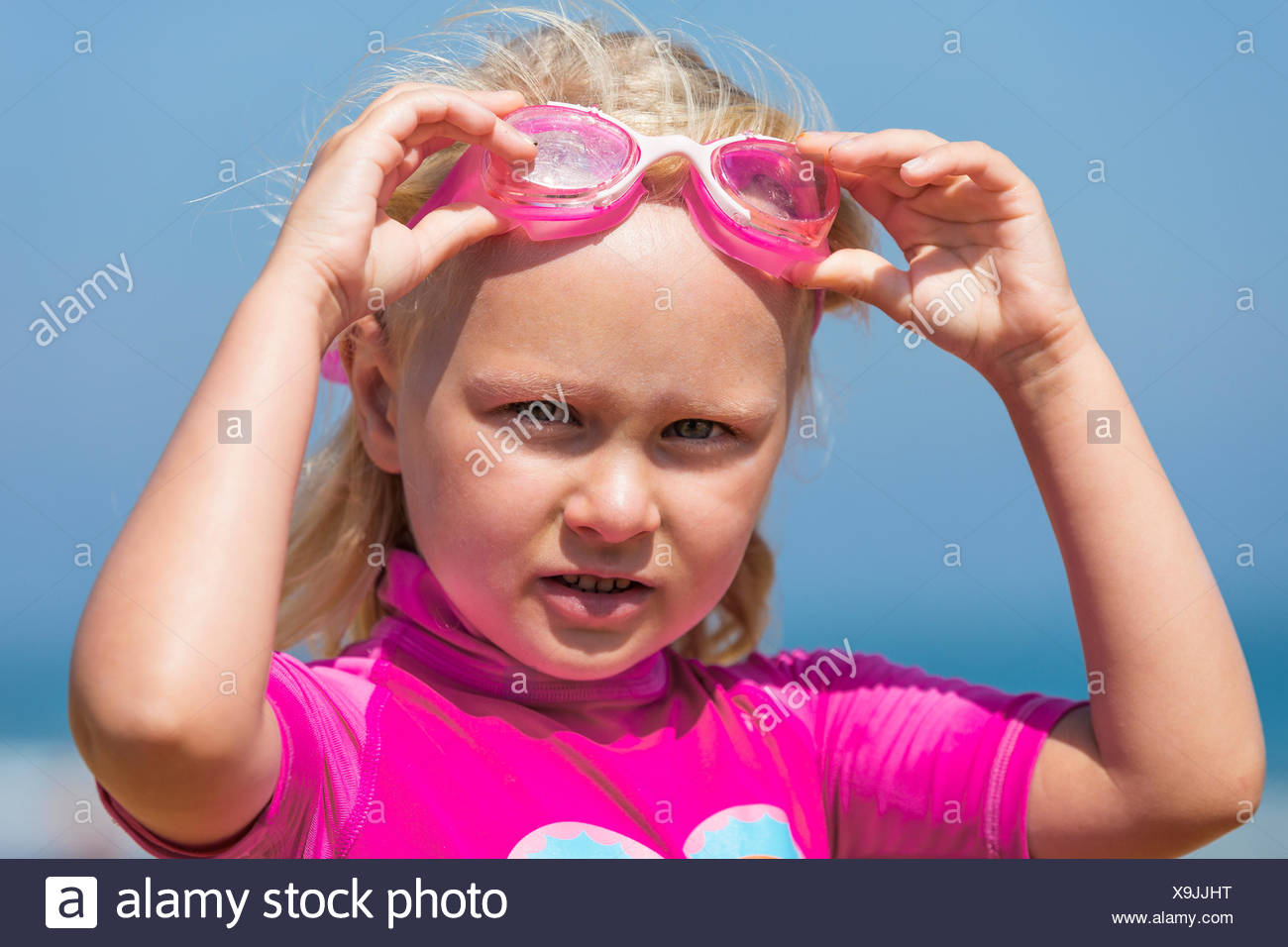 little girl at the beach in an anti-UV swimsuit putting her pink goggles on - Stock Image