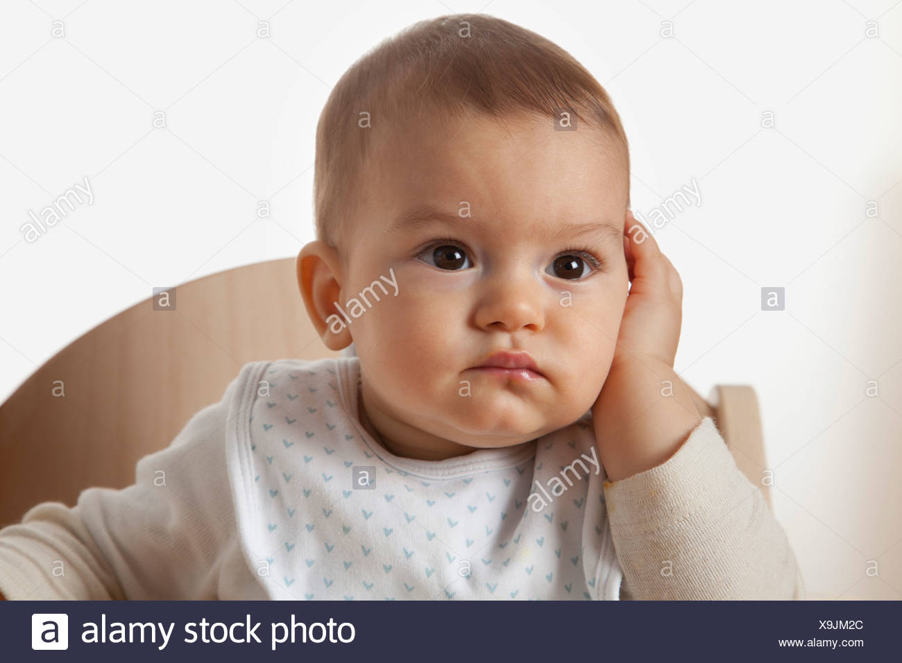 portrait of baby in high chair looking astonished - Stock Image