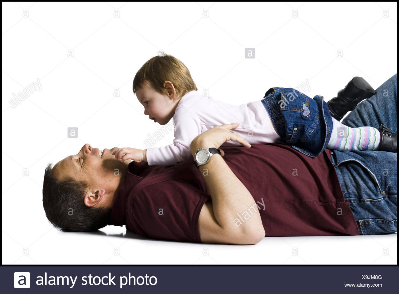 Side profile of man with baby girl snuggling - Stock Image