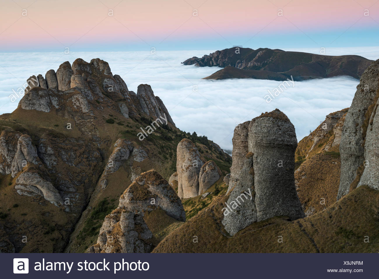 Thick cloud cover rolls to the base of conglomerate rock formations in the Ciucas mountains. - Stock Image