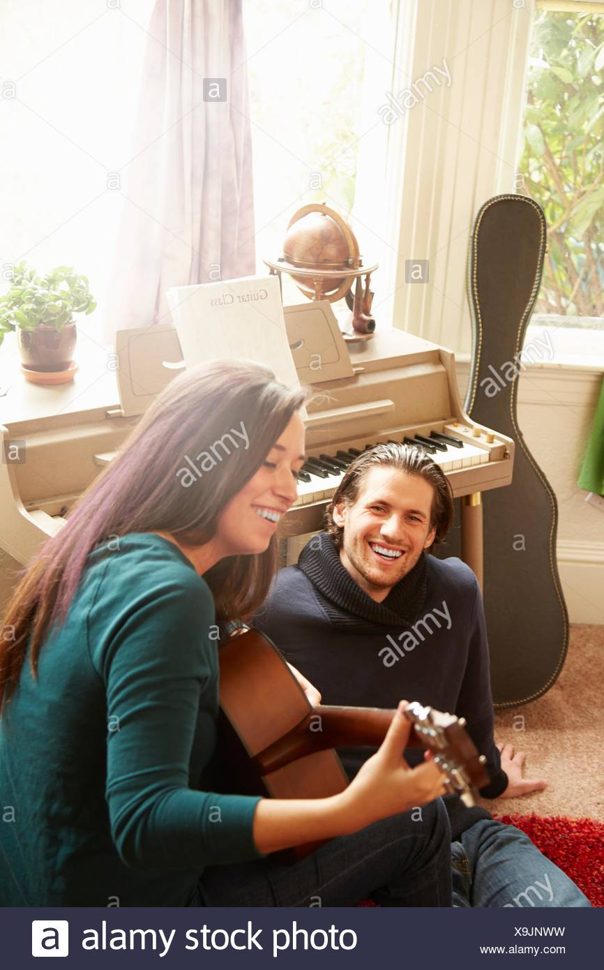 Young couple playing acoustic guitar in living room - Stock Image