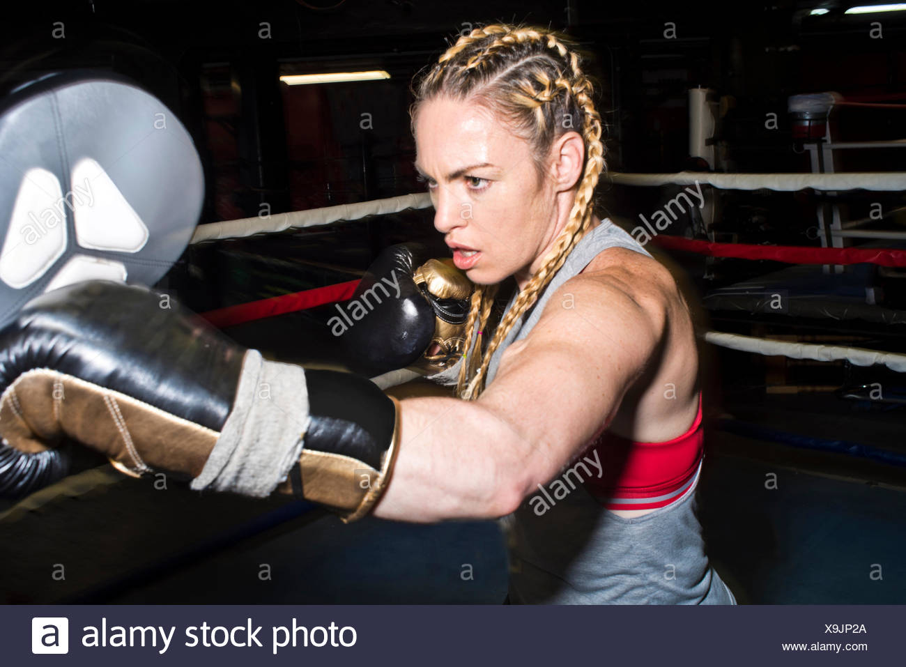 Female boxer punching boxing mitt in boxing ring - Stock Image