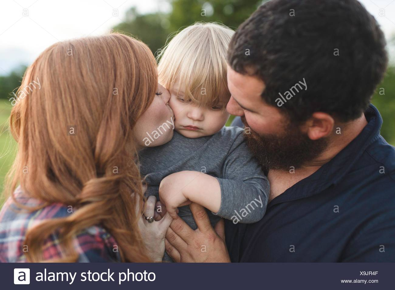 Mother and father holding young son, outdoors - Stock Image