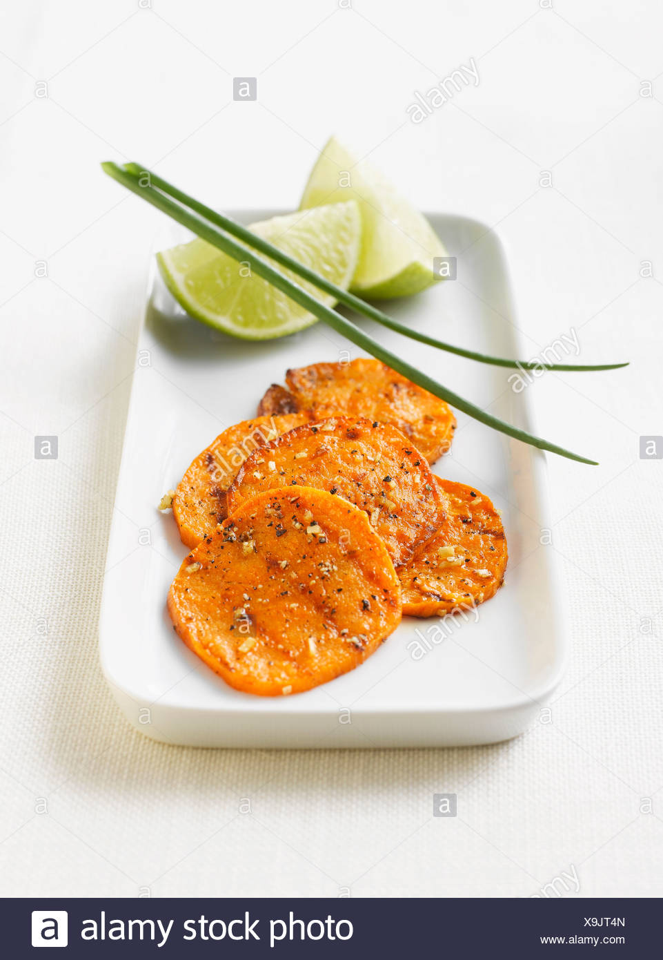 Grilled potato slices with lime slices and chive on platter - Stock Image