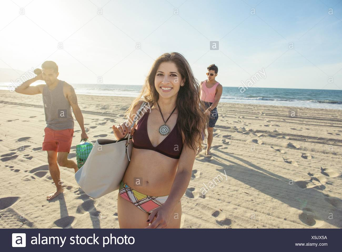 Group of friends walking on beach - Stock Image