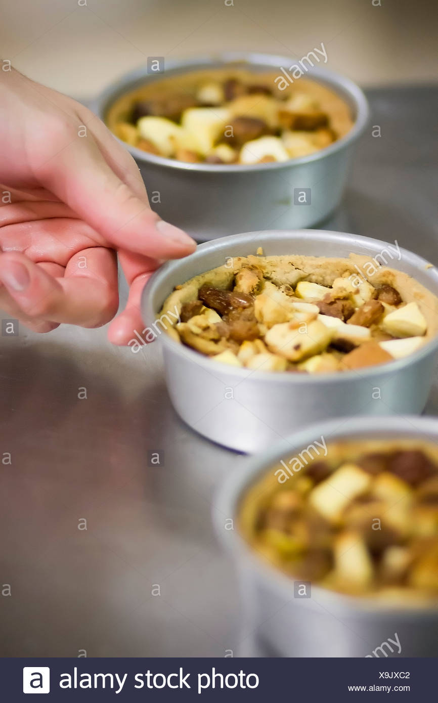 Baker with tins of nut cake - Stock Image