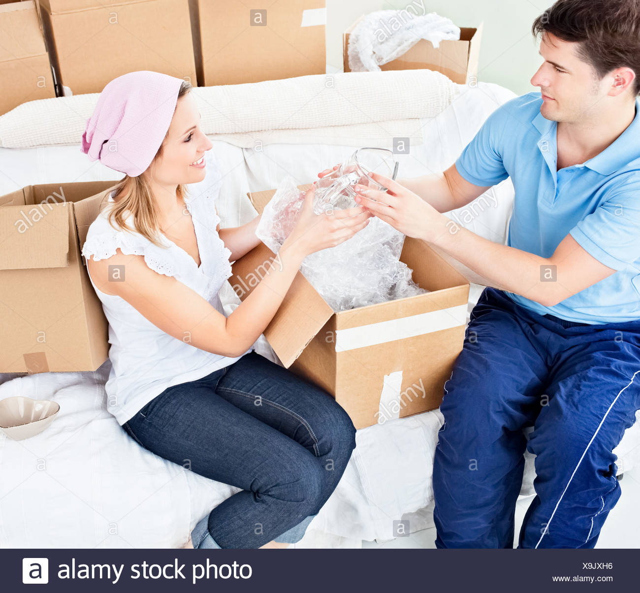 Affectionate young couple unpacking boxes with glasses - Stock Image