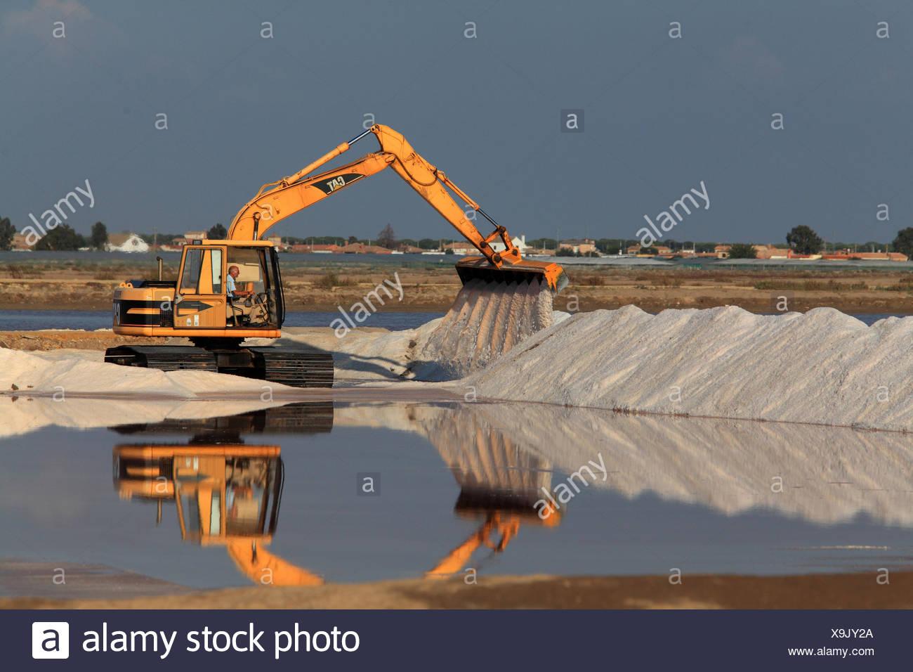 excavator shoveling salt, salt production of a saline, Spain, Sanlucar de Barrameda - Stock Image