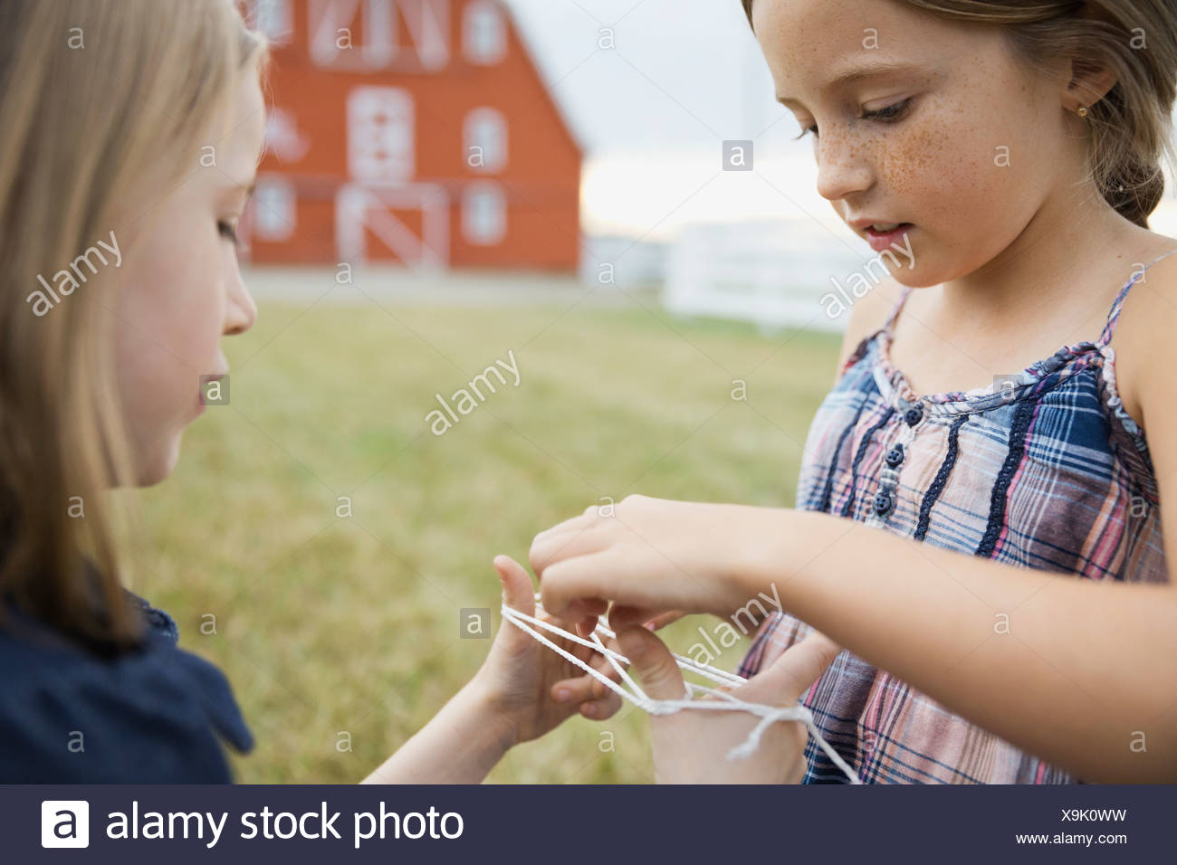 Little girls playing cats cradle outdoors - Stock Image