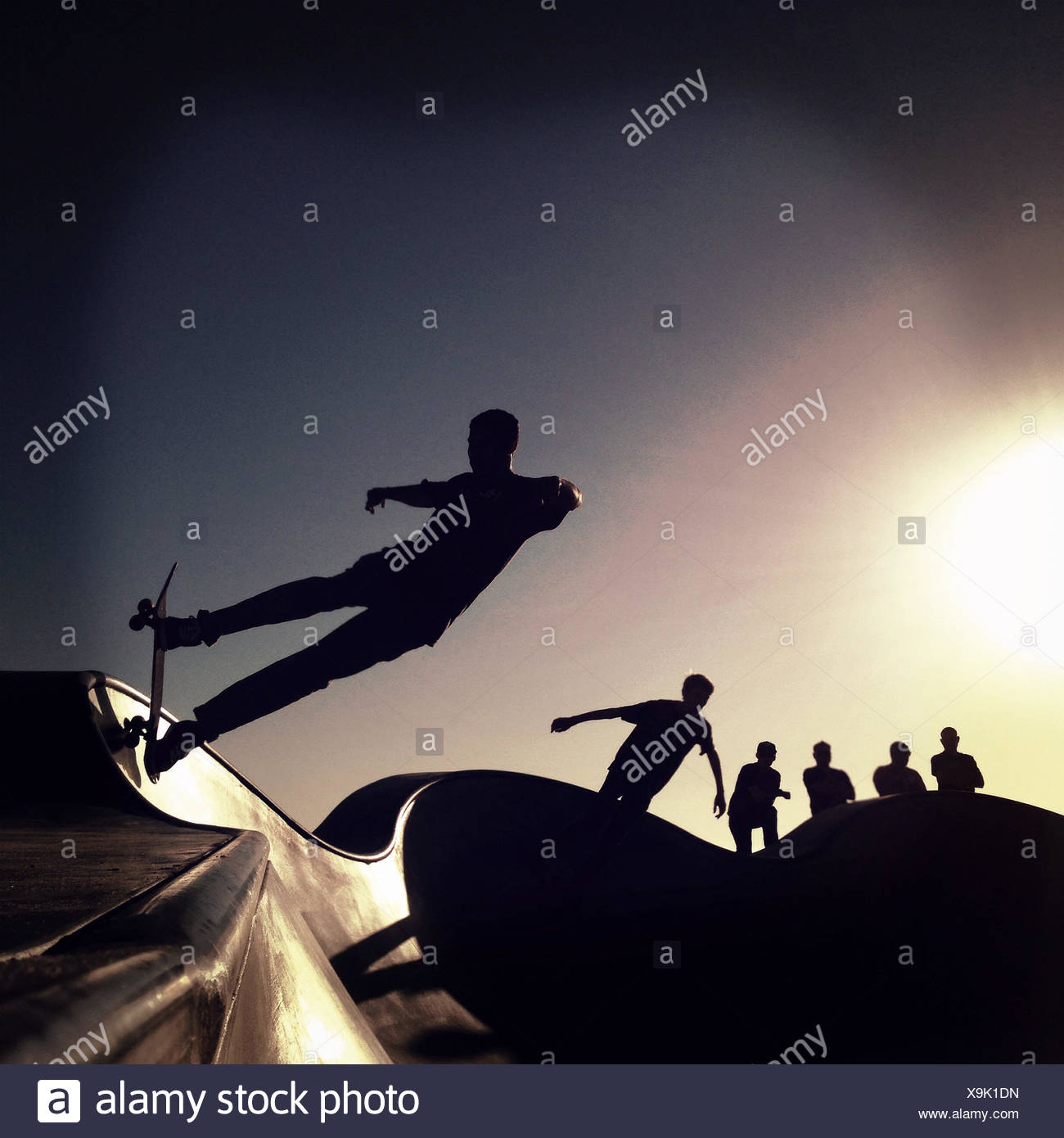Silhouette of skaters in skateboard park at sunset - Stock Image