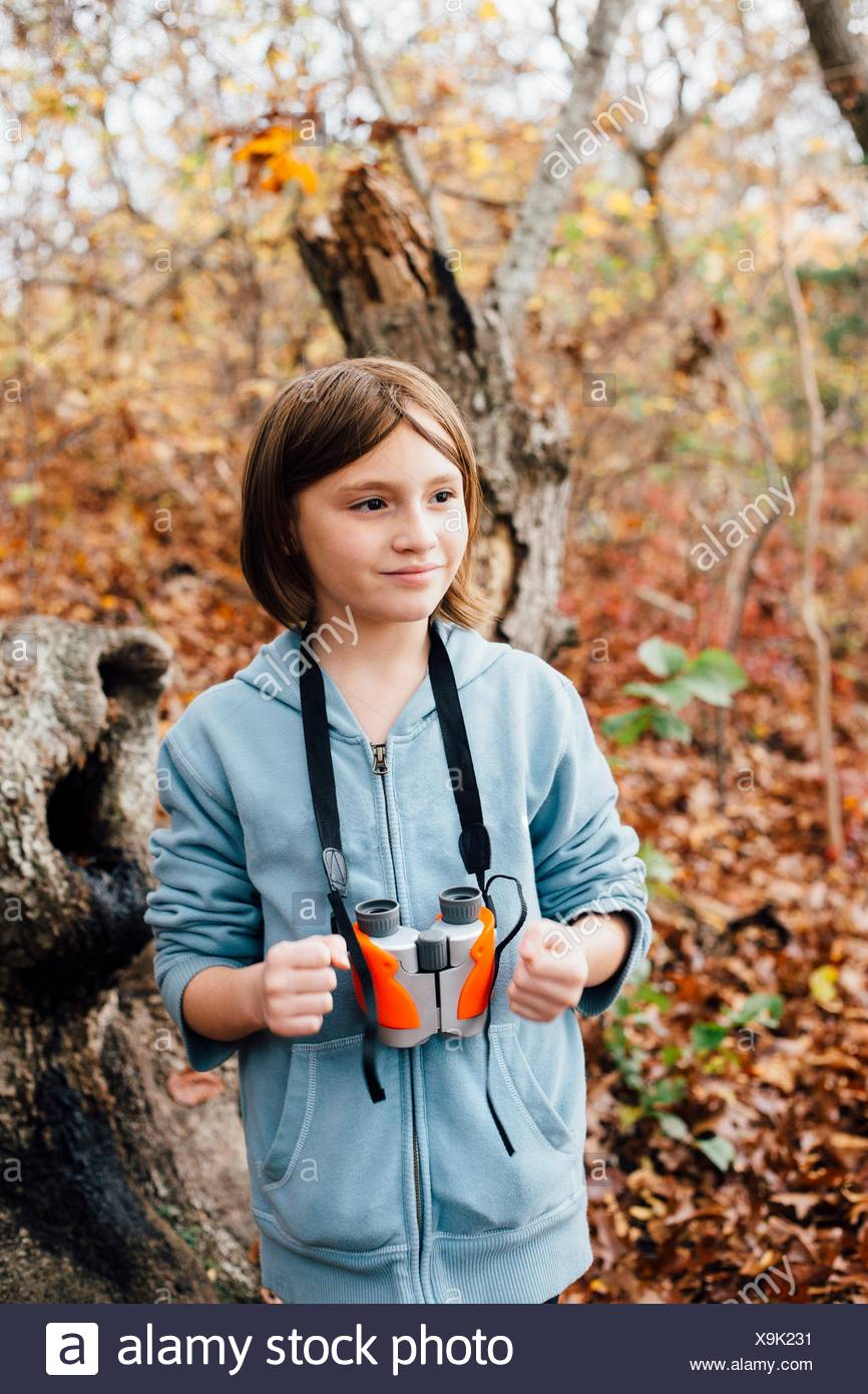 Young girl in forest, binoculars round neck - Stock Image