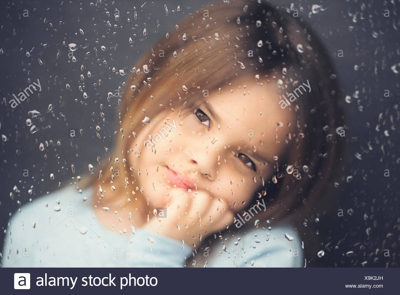 Girl looking out of a window on a rainy day - Stock Image