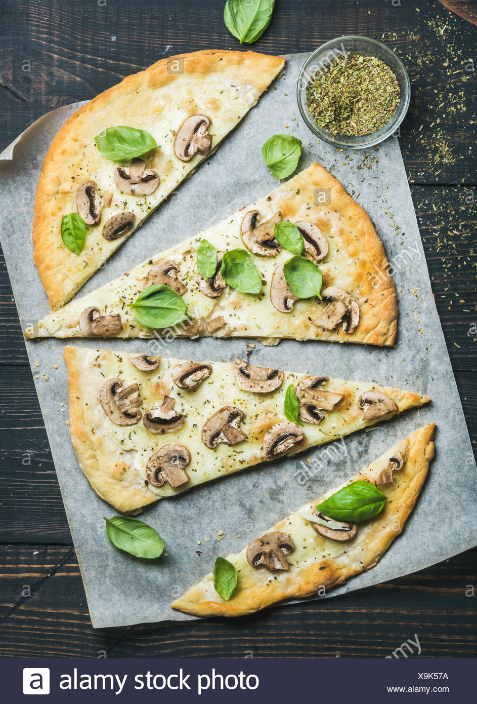 Homemade sliced mushroom pizza with basil and spices in glass on baking paper over dark scorched wooden background, top view, ve - Stock Image