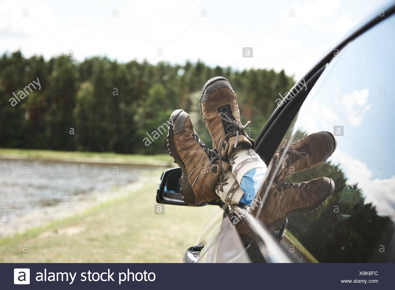 Woman relaxing in car, feet through open window, focus on feet - Stock Image
