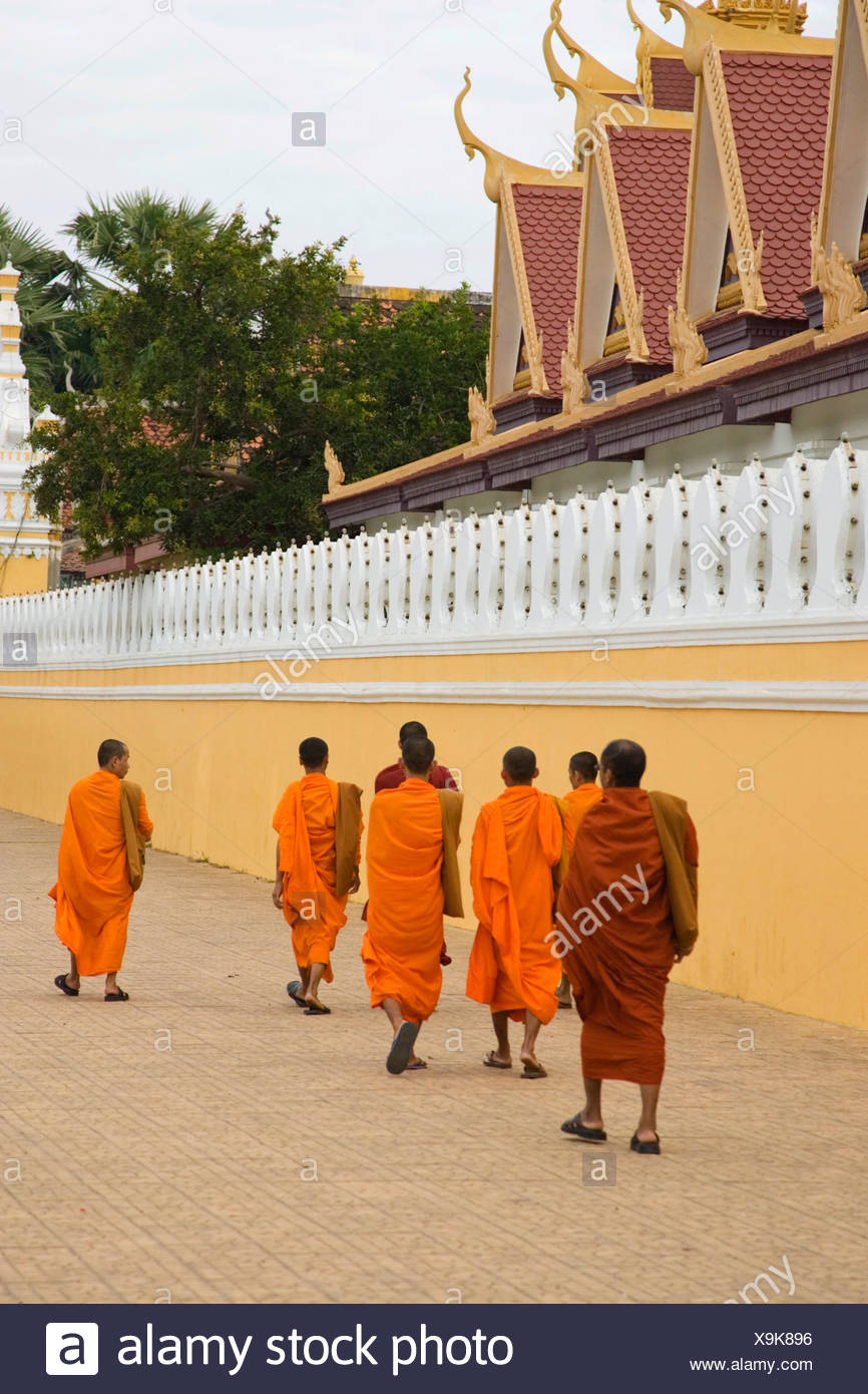 Buddhist monks dressed in orange robes walk along the wall of the Royal Palace, Phnom Penh, Cambodia - Stock Image