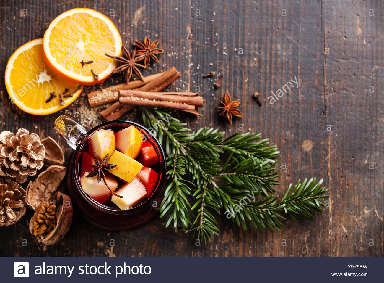 Cup of hot wine with spices on wooden background - Stock Image