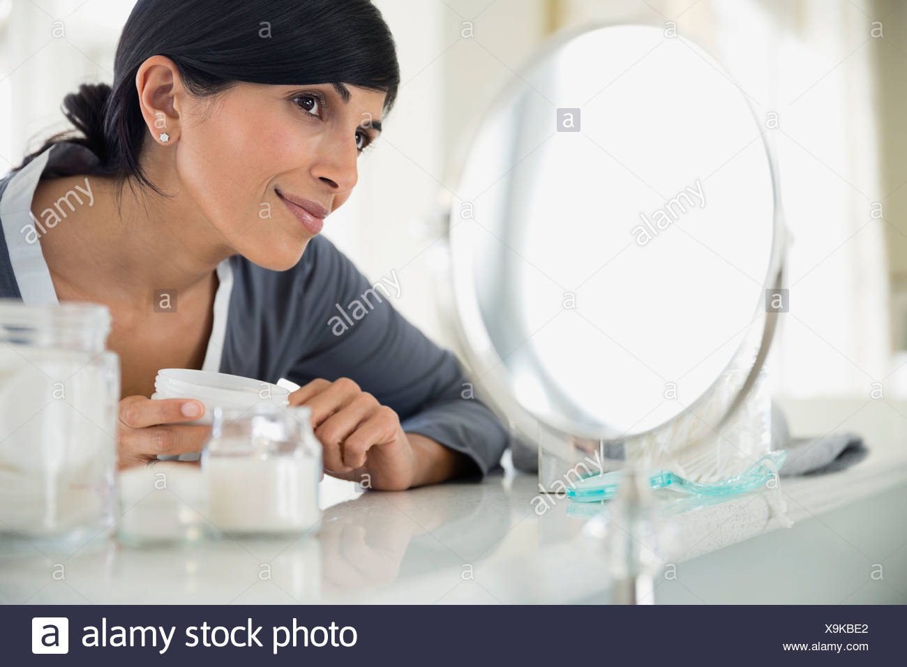 Beautiful woman holding cream bottle while looking in mirror at dressing table - Stock Image