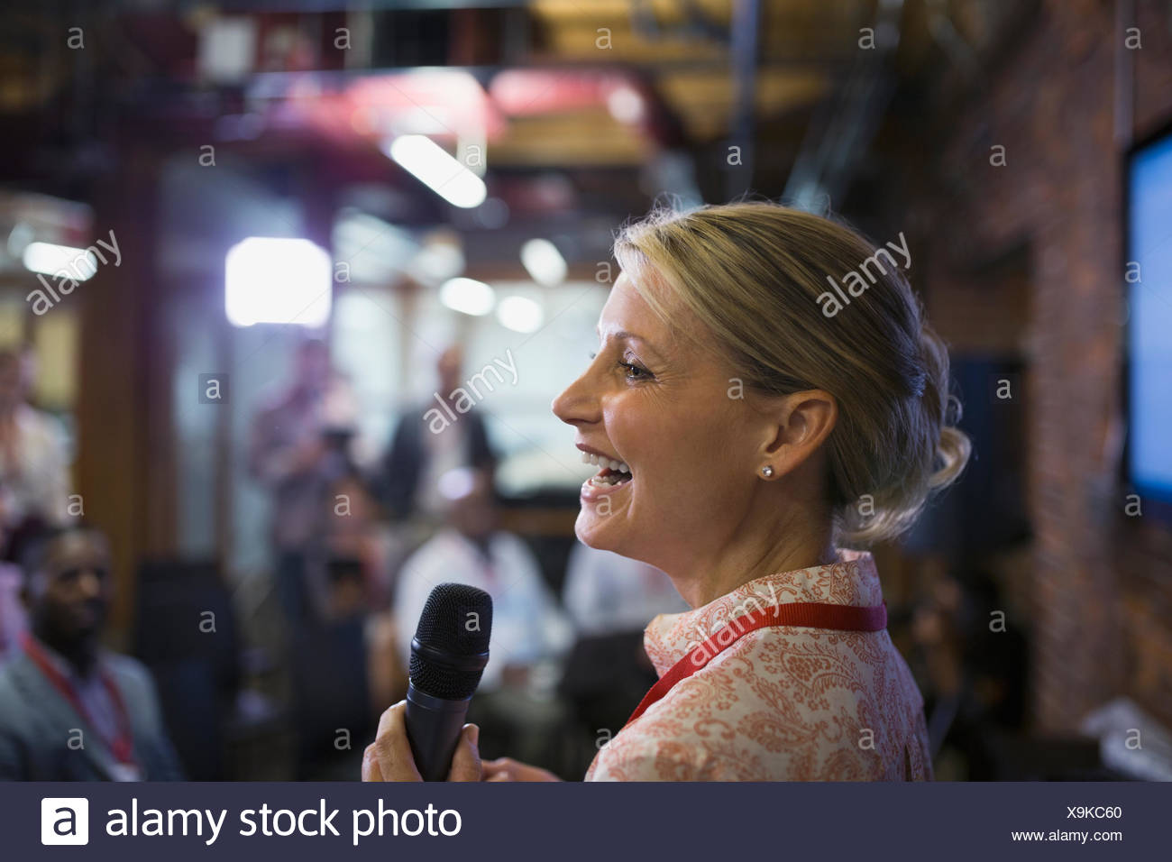 Close up businesswoman with microphone speaking at conference - Stock Image