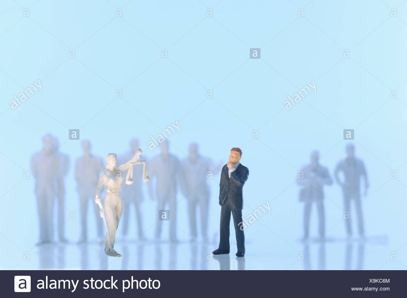Figurine of justice and businessman on blue background Stock Photo