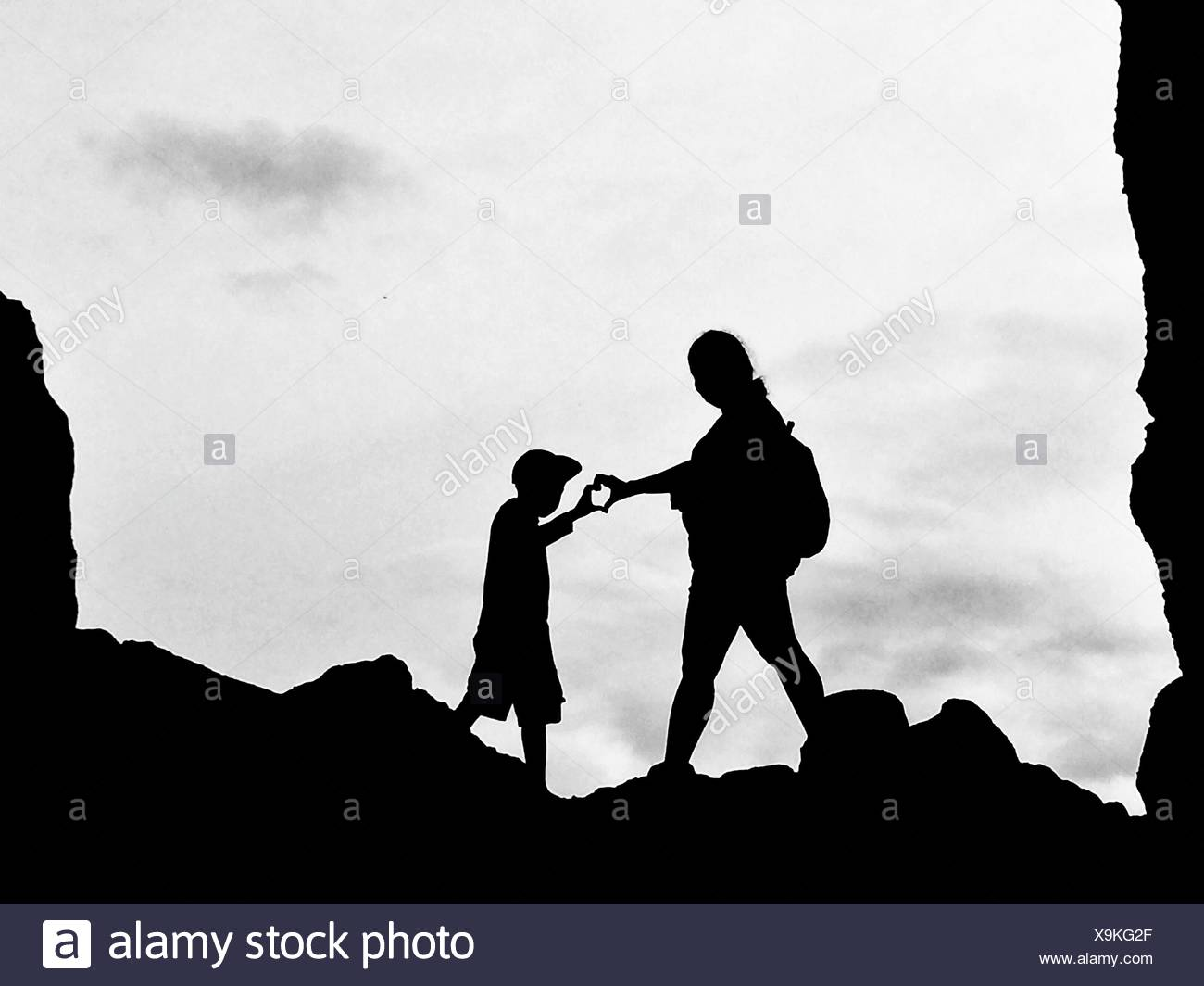 Low Angle View Of Silhouette Mother And Son Making Heart Shape With Hand - Stock Image