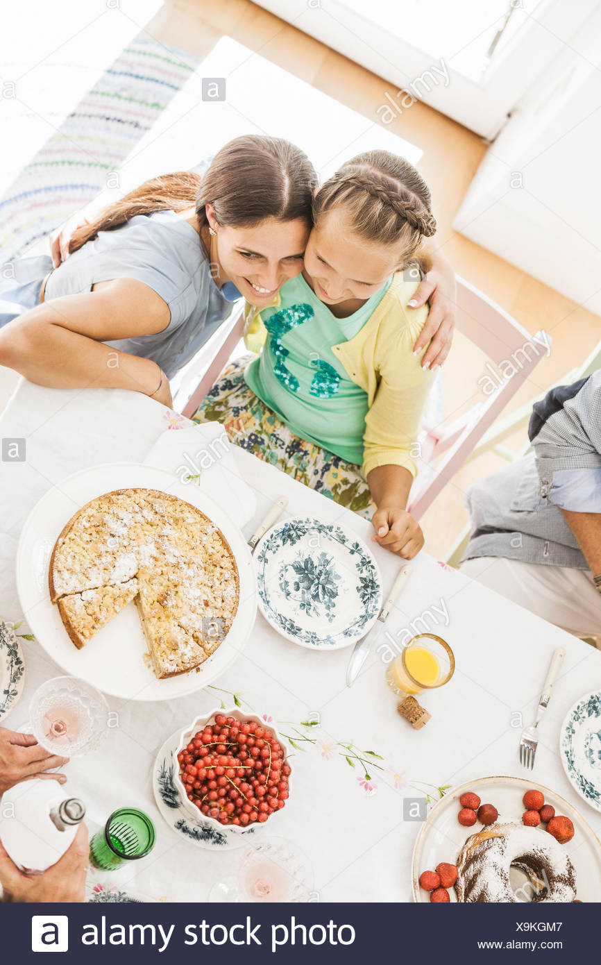 Overhead view of mother hugging daughter at birthday party - Stock Image