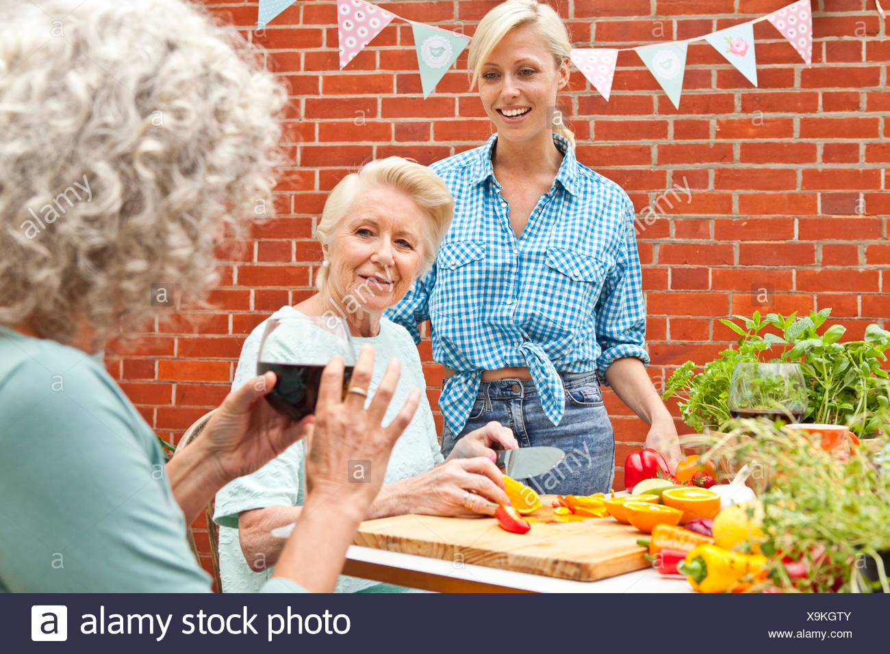 Three generation women chatting while preparing food at garden table - Stock Image