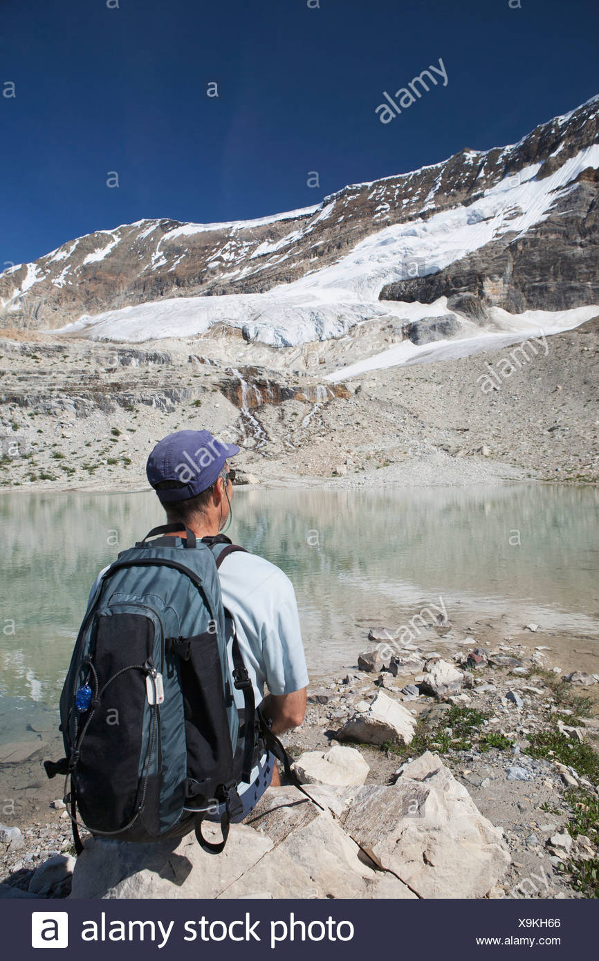 Male Hiker Sitting On A Rock With Glacier On Mountain Side Streaming Down Into A Reflective Mountain Pond, British Columbia - Stock Image