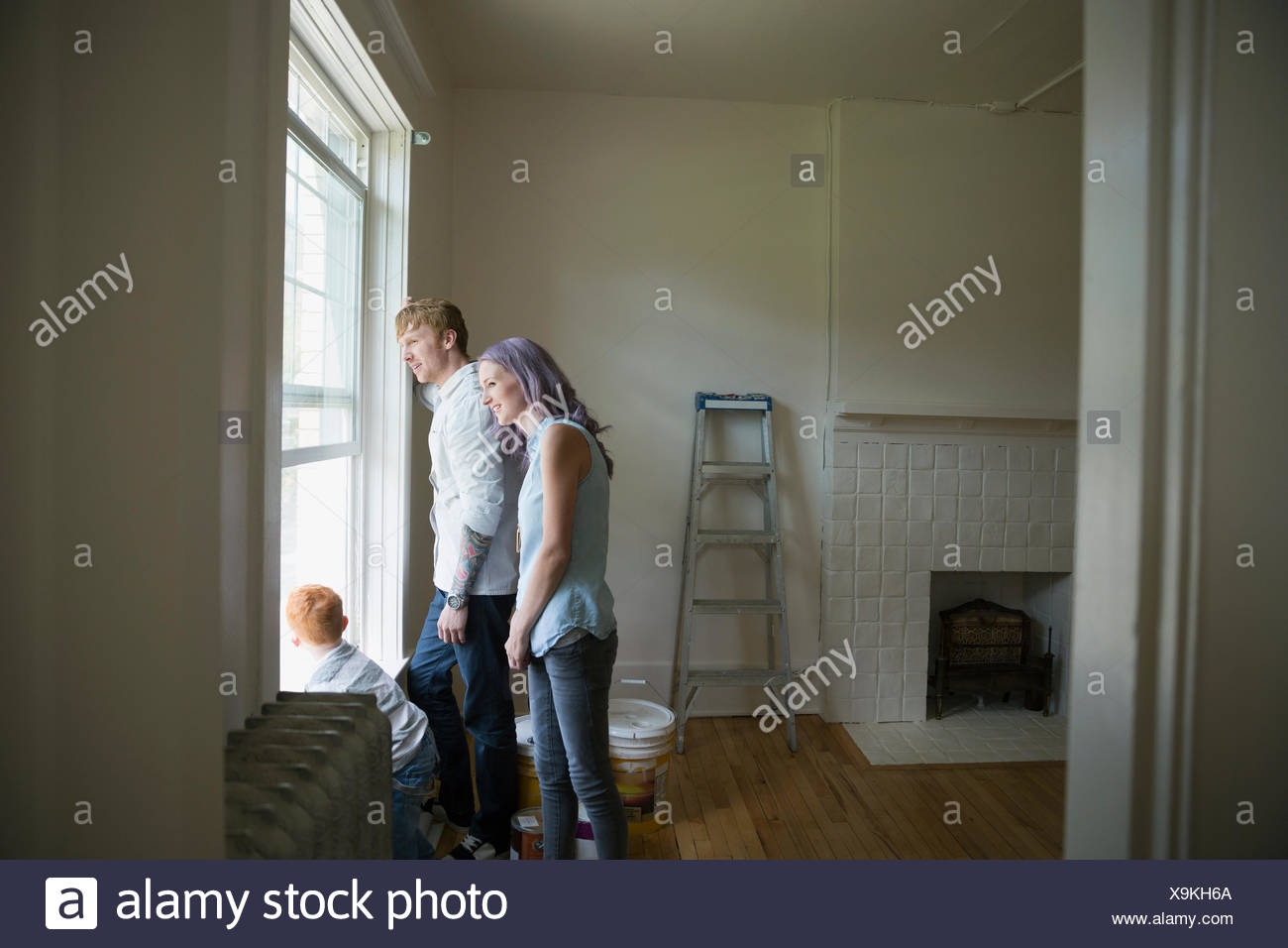 Young family looking out window in new house - Stock Image
