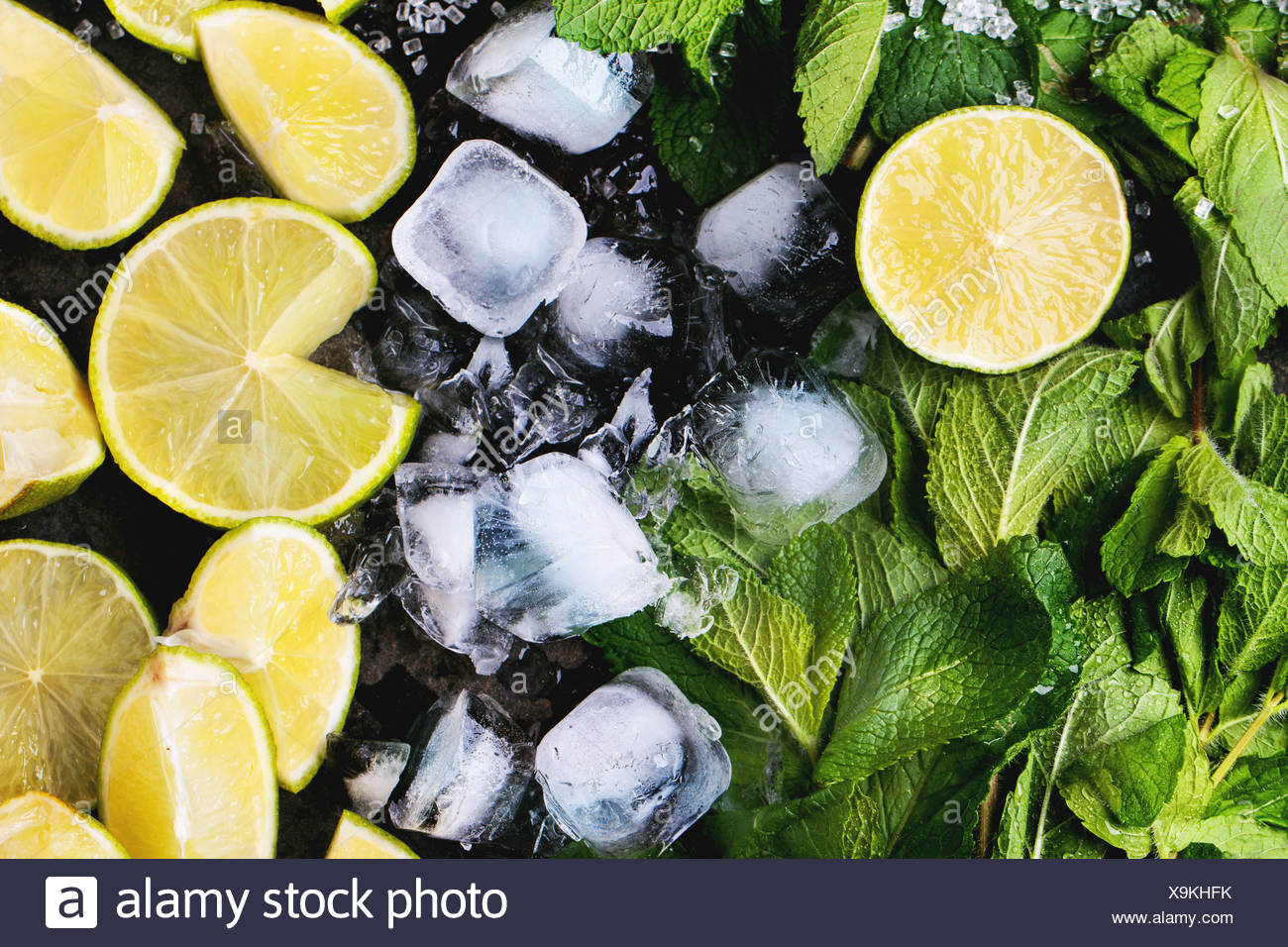 Ingredients for mojito (fresh mint, limes, ice) over black. - Stock Image