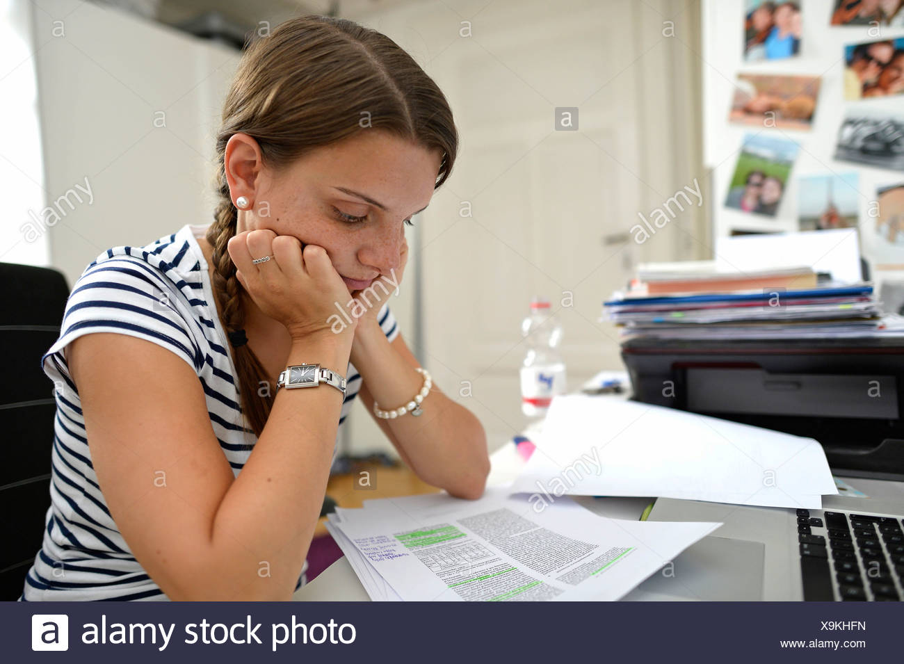 Student learning in a college dorm, pondering, thinking - Stock Image