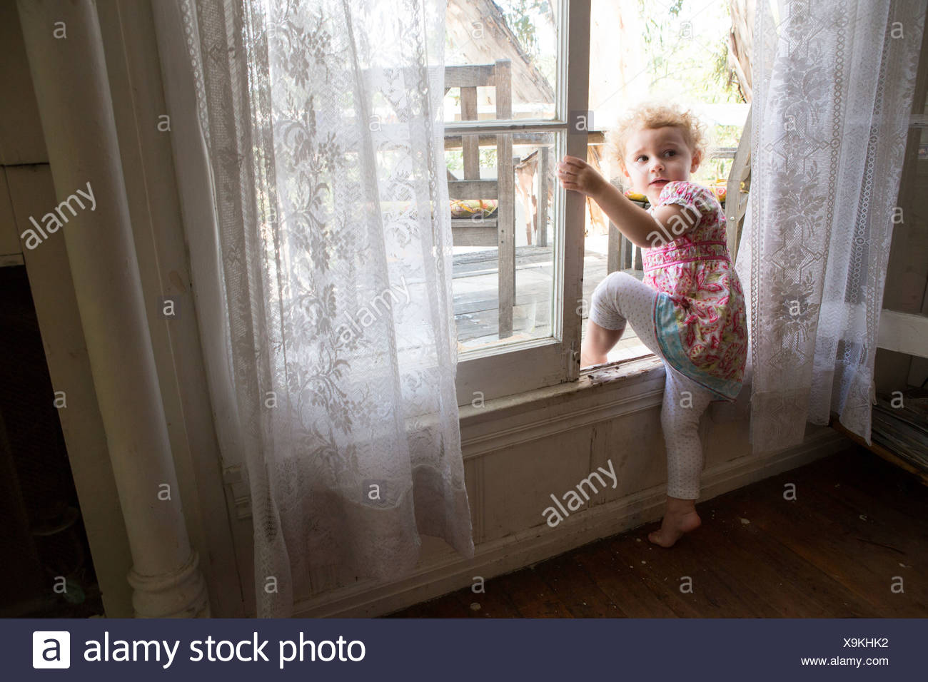 Child climbing over opened window - Stock Image