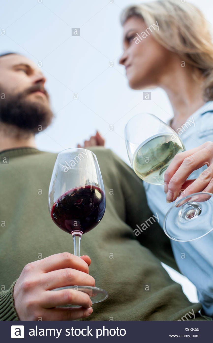 Heterosexual couple drinking wine in garden party - Stock Image