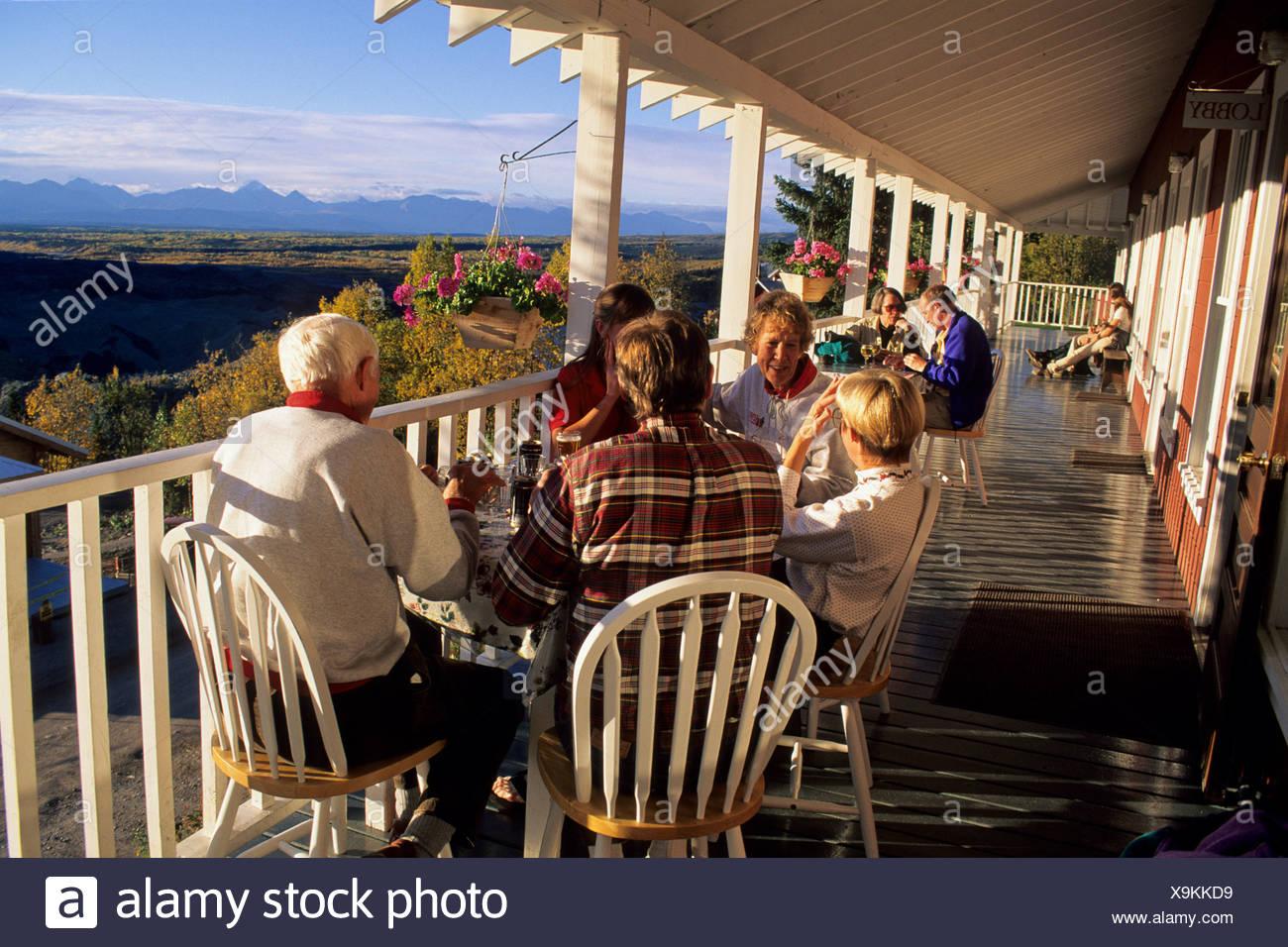Alaska. Wrangell St Elias National Park. McCarthy People enjoy dining on a deck. - Stock Image