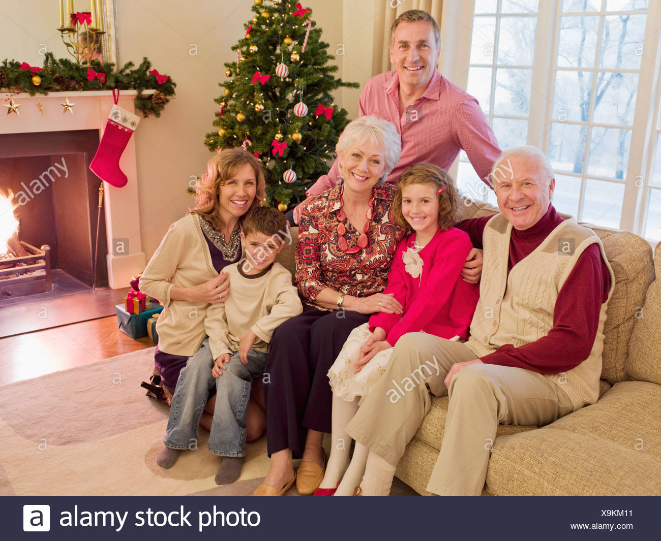 Multi-generation family near Christmas tree in living room Stock Photo