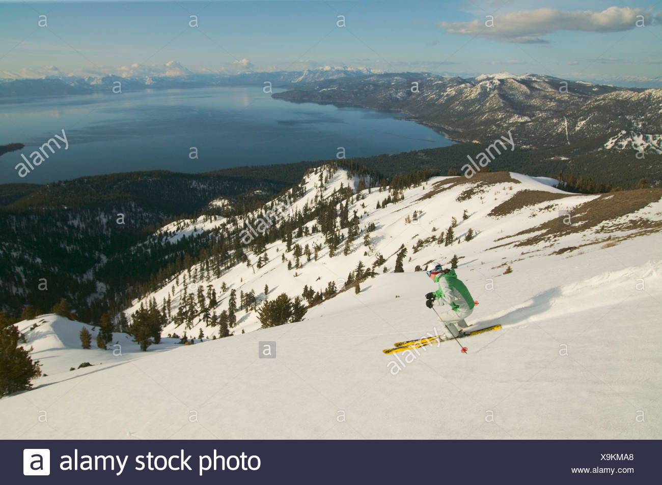 A woman skiing above Lake Tahoe CA at sunset - Stock Image
