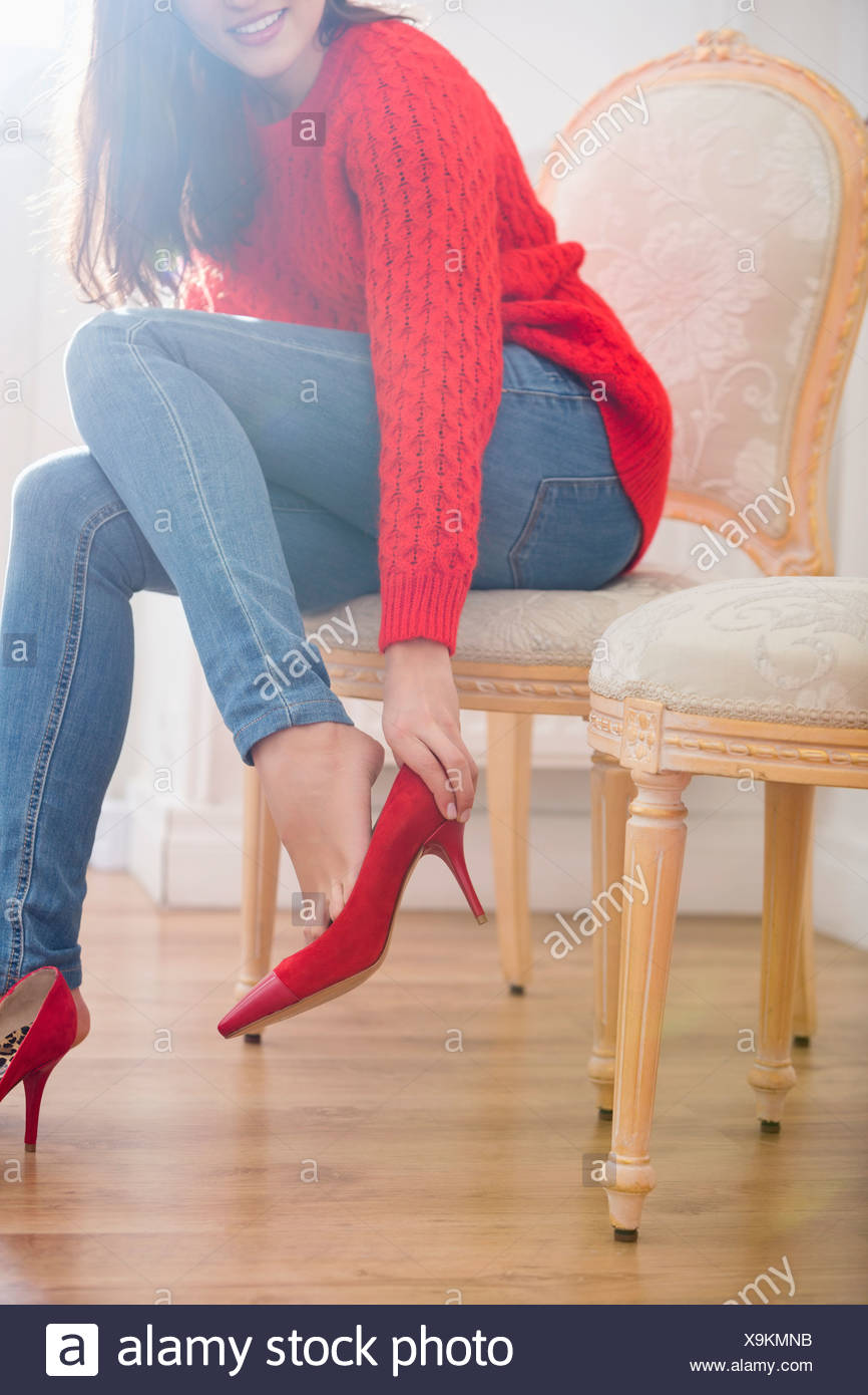 Low section of woman trying on footwear in store - Stock Image